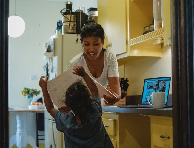 Parent and child in kitchen trying to work from home and home school child
