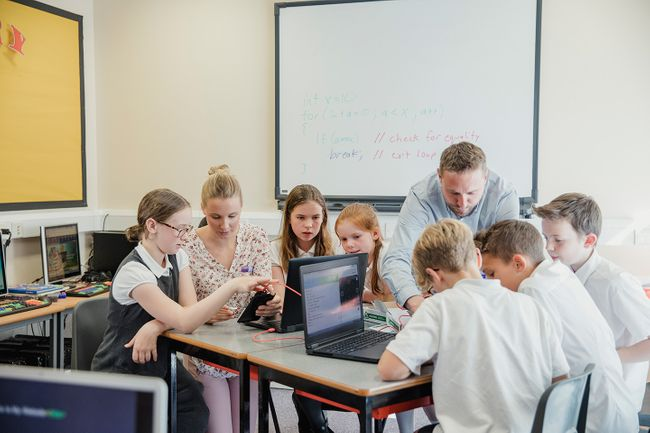 Two teachers working with their students on laptops in a classroom environment