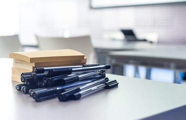 Pile of post-its and a pile of pens on a desk in a classroom